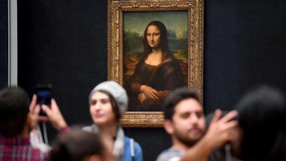 Besucher lassen sich vor der Mona Lisa im Louvre fotografieren