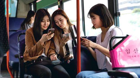 Drei weibliche Teenager sitzen in Seoul im Bus und jeder guckt auf sein Handy