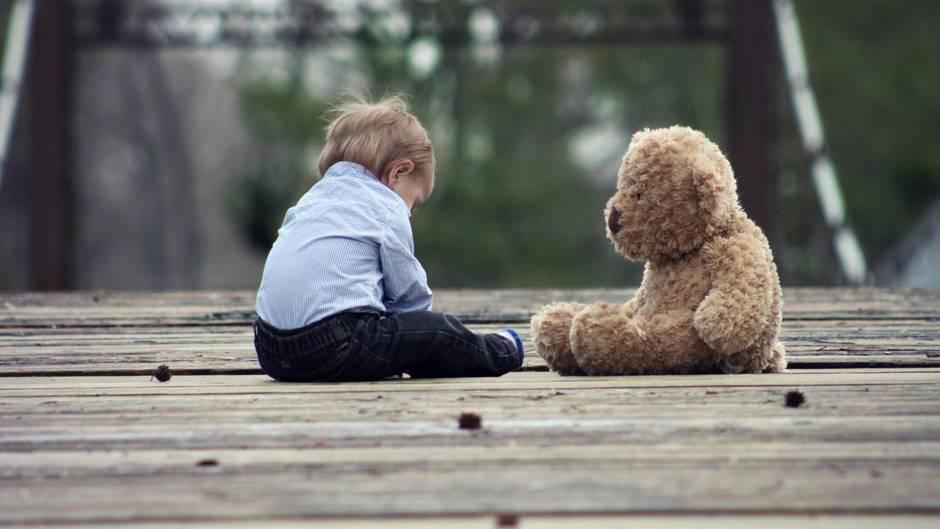 Ein kleiner Junge sitzt neben einem großen Teddy