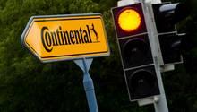 """Ein rote Ampel neben einem Schild mit der Aufschrift """"Continental"""" vor einem Werk in Gifhorn"""