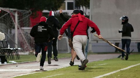 Hooligans von Olymiakos Piräus stürmen aus dem Stadion, nachdem sie Bayern-Fans angegriffen haben