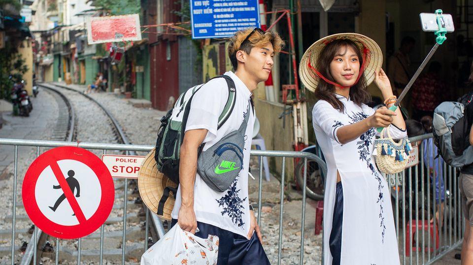 """Vietnam, Hanoi: Ein Paar macht ein Selfie an der Absperrung zur """"Train Street"""""""