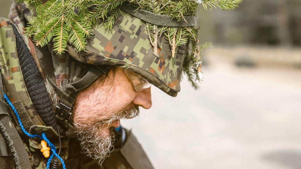 Ein Soldat mit Tannenzweigen auf dem Helm