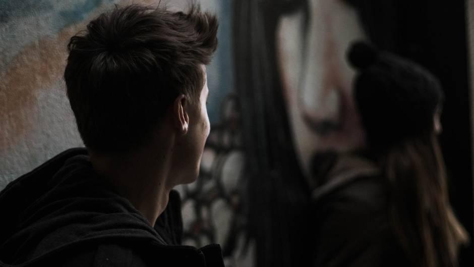 Ein schüchterner junger Mann schaut ein Mädchen an