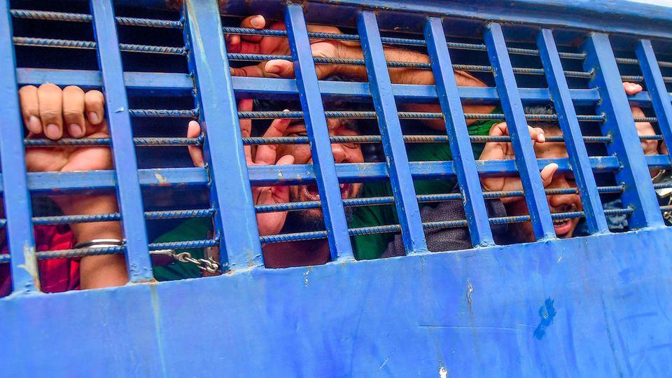 Durch die blauen Gitter eines Gefangenentransporters ist das verzweifelt Gesicht eines Mannes zu sehen