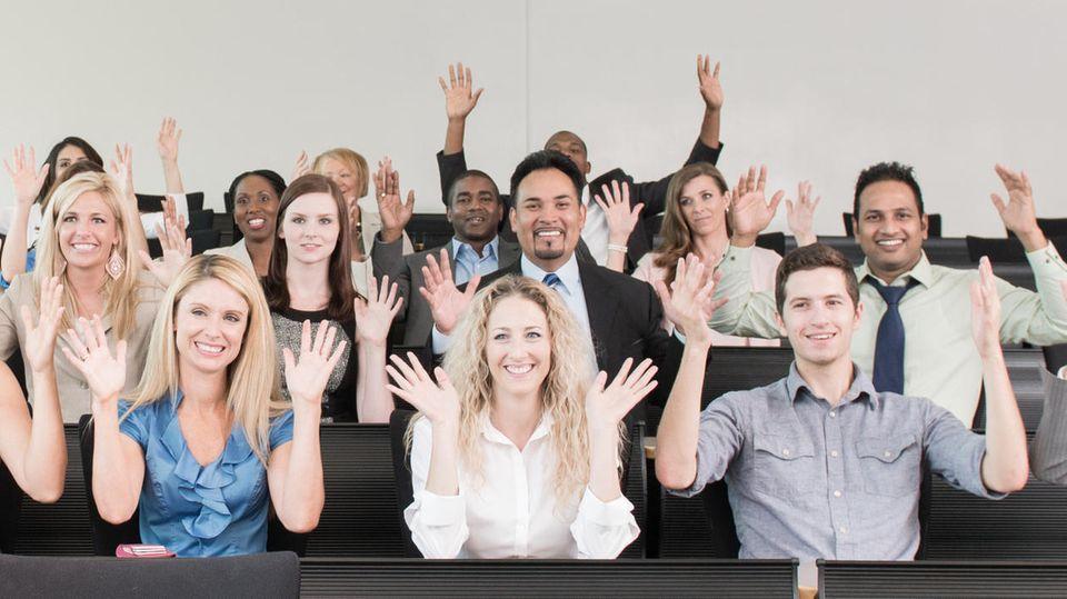 Menschen halten Hände über den Kopf und winken