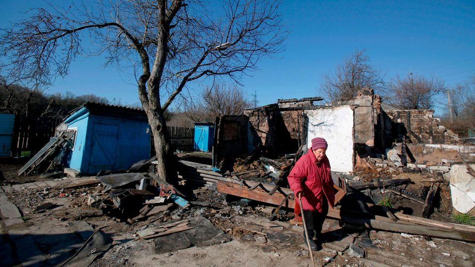 Eine alte Frau vor einem zerstörten Hausin der Ostukraine