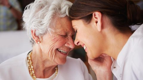 Eine Seniorin lacht gemeinsam mit einer Pflegerin