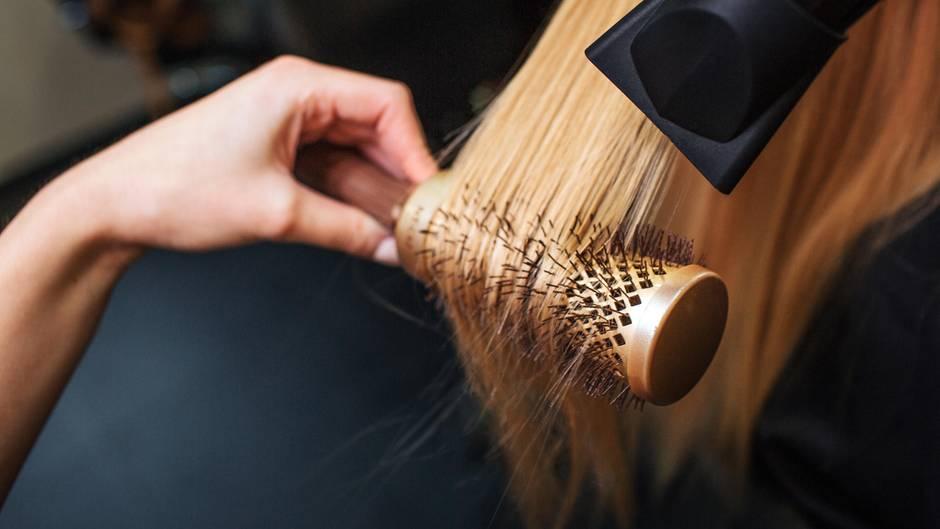 Eine Friseurin trocknet das Haar einer Kundin über einer Rundbürste mit dem Fön