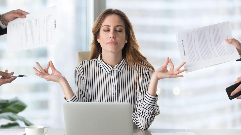 Eine Frau sitzt offensichtlich tiefenentspannt vor ihrem Laptop am Schreibtisch und bekommt von allen Seiten Aufgaben zugeteilt