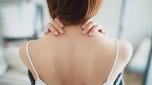 Eine Frau reibt sich wegen einer Muskelverärtung den Nacken