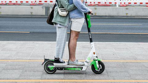 Zwei Personen fahren gemeinsam gleichzeitig auf einem E-Tretroller