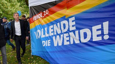 """Neben einem blauen Tuch mit dem Slogan """"Vollende die Wende"""" steht AfD-Spitzenkandidat Björn Höcke"""