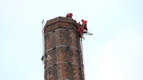 Einsatzkräfte bergen den leblosen Körper des Mannes von dem mehr als 80 Meter hohen Schornstein