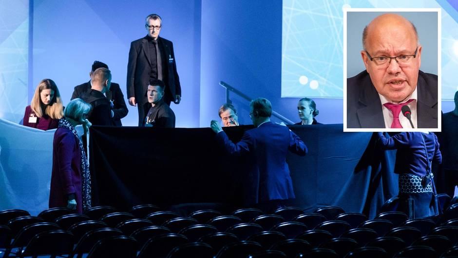 Helfer schirmen Bundeswirtschaftsminister Peter Altmaier nach seinem Sturz mit schwarzen Tüchern ab