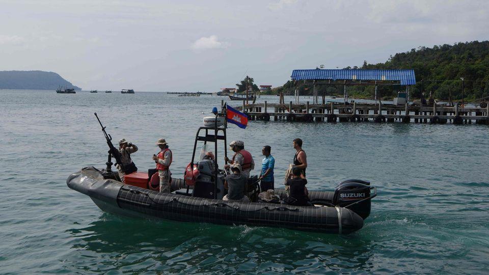 Taucher und Soldaten fahren mit einem Boot raus aufs Meer