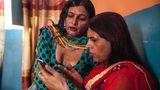 Zwei Transgender-Frauen bedienen ein Mobiltelefon