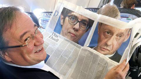 """NRW-Ministerpräsident Armin Laschet liest im Flugzeug einen Zeitungsartikel über """"Das Duell"""" zwischen AKK und Merz"""