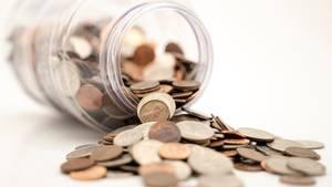 Münzen fallen aus einem Glas