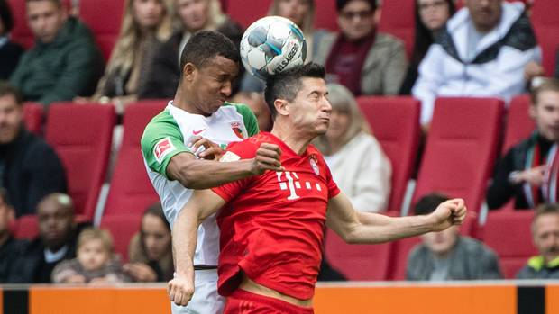 Bayern-Stürmer Robert Lewandowski und Augsburgs Felix Uduokai im Luftkampf