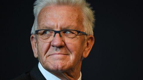 Ein Mann mit weißem Igelschnitt und schwarzem, eckigen Brille schaut mit nach rechts gedrehtem Kopf aus den Augenwinkeln
