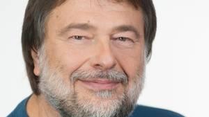 Ein Mann mit braunem Seitenscheitel und grau-weißem Vollbart lächelt in die Kamera