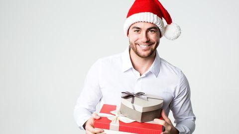 Lächelnder Mann in Nikolausmütze mit Geschenk-Boxen