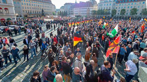 Teilnehmer einer Kundgebung von Pegida und Teilnehmer von Gegenkundgebungen stehen auf dem Altmarkt in Dresden