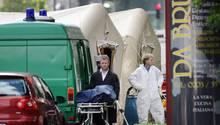 Ein Bestatter schiebt eine Trage mit einer verdeckten Leiche von einem Tatort