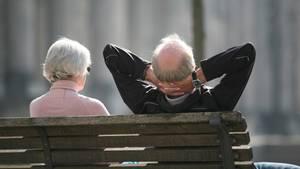Ein Rentnerpaar sitzt auf einer Bank