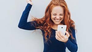 Frau freut sich über Smartphone