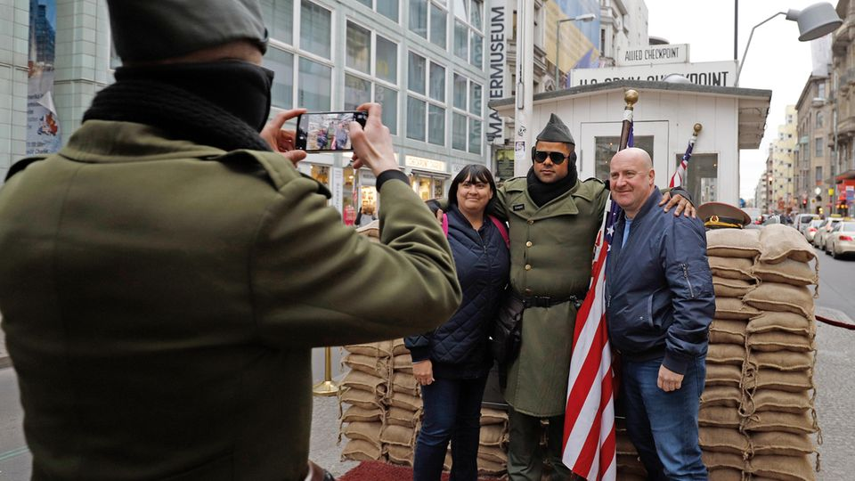 Zwei Touristen aus England lassen sich am Checkpoint Charlie mit einem Mann in US-Uniform fotografieren