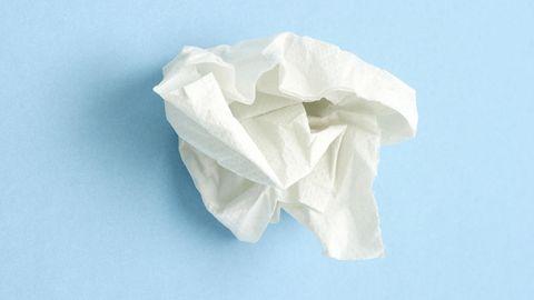 Erkältung: Ein zerknülltes Taschentuch liegt auf blauem Untergrund