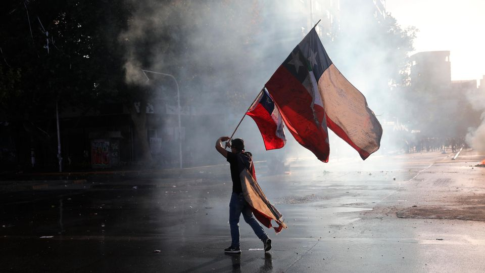 Ein regierungskritischer Demonstrant schwenkt während eines Protests eine chilenische Fahne