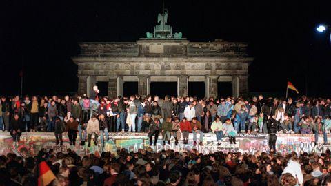 Feiernde Ost- und Westdeutsche auf der Berliner Mauer am Brandenburger Tor in der Nacht des 9. November 1989