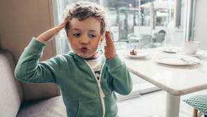 Ein Junge hält sich die Hände über die Ohren