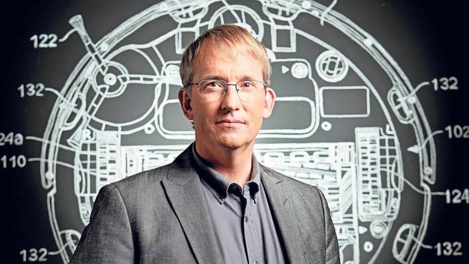Colin Angle vor der Konstruktionszeichnung eines Saugroboters.