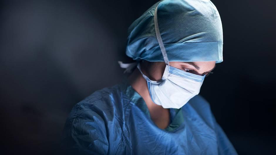 Gehirnschaden nach Magen-OP: Eine junge Frau steht im OP und operiert