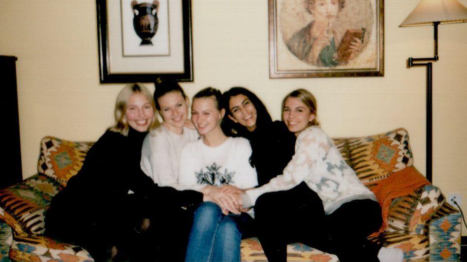 Die Autorin mit ihren vier besten Freundinnen sitzen auf einem Sofa und lachen in die Kamera