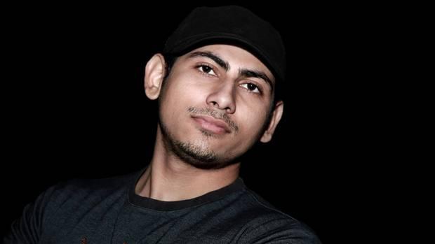 Ein schwarz gekleideter junger Inder macht ein Selfie