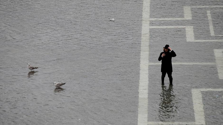 Ein Mann macht bei Hochwasser auf dem Markusplatz von Senedig ein Selfie