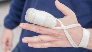 Ein Mann hat eine Mullbinde um den Finger gewickelt