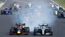 Max Verstappen im Red Bull (l.) und Valtteri Bottas im Silberpfeil liefern sich beim Start in Ungarn ein enges Duell