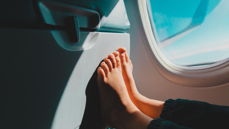 Ein Kind sitzt im Flugzeug und hat die nackten Füße gegen den Vordersitz gepresst