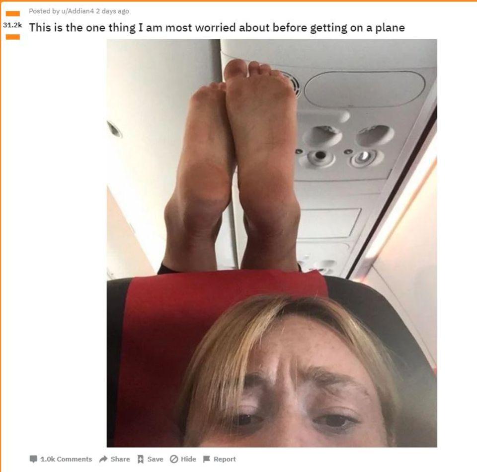 Ein Selfie zeigt eine Frau im Flugzeug, hinter hier die nackten Füße ihres Sitznachbarn