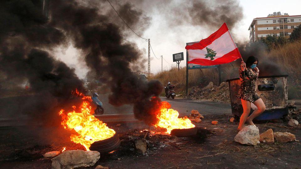 Eine Teilnehmerin einer Demonstration geht mit einer Libanon-Fahne und Mundschutz an brennenden Reifen vorbei