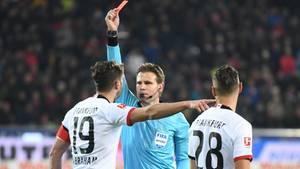 Schiedsrichter Felix Brych zeigt David Abraham nach einem Foul an Freiburg Coach Christian Streich die rote Karte