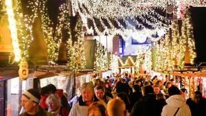 Besucher eines Weihnachtsmaktes gehen an Buden vorbei