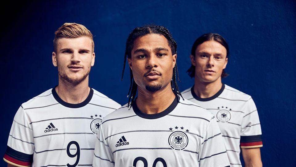 Timo Werner, Serge Gnabry und Nico Schulz stehen vor einem blauen Hintergrund und schauen in weißen Fußball-Trikots geradeaus