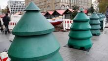 Als Weihnachtsbäume verkleidete Beton-Durchfahrtssperren stehen vor dem Eingangsbereich eines Weihnachtsmarktes